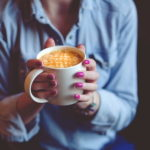寒い冬に温かいカフェラテを飲んで身体を温めている女性