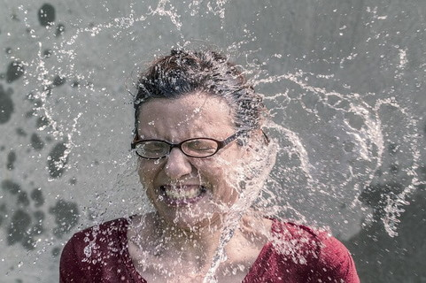 思うように水分補給ができずに水しぶきを浴びて水分補給をしようとしている女性