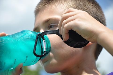 甘くて美味しいスポーツドリンクをがぶ飲みしている少年