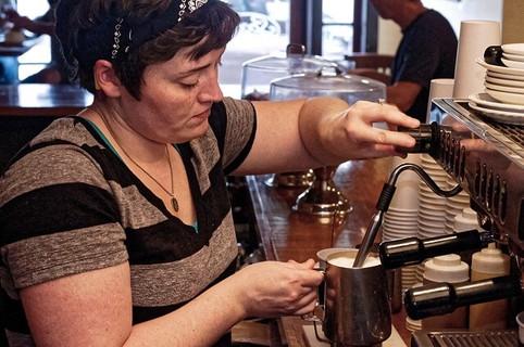 キッチンで身体の温まりそうなホットドリンクを作っている女性