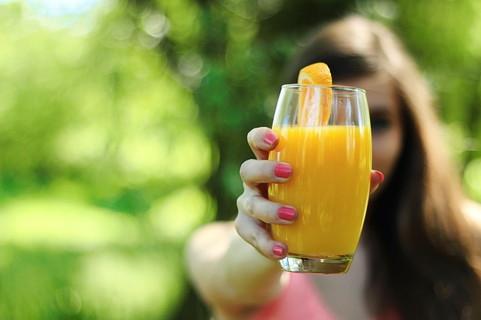 グラスに注がれた美味しそうな飲み物を水分補給するように差し出す女性
