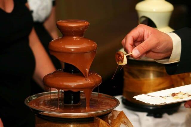 自宅で美味しそうなチョコレートフォンデュを用意してバレンタインのおもてなしをする女性