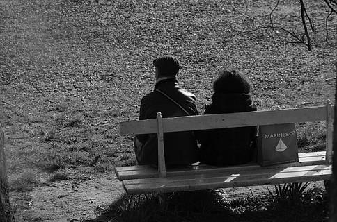 マッチングサイトで念願叶って会うことが出来て恥ずかしそうに公園のベンチで話をする男女