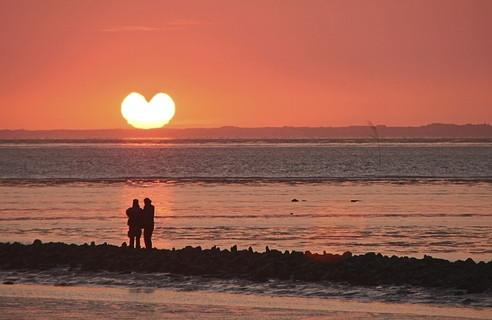 ハートの形をした夏の夕日を海辺で眺める幸せそうなカップル